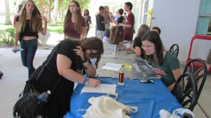 Abby Sadler, freshmen, signs up for the Thespian Club during Freshman Invasion. During lunch at orientation, freshmen were given the opportunity to look at some of the clubs the school offers, meet the clubs' representatives and sign up for extracurricular activities.